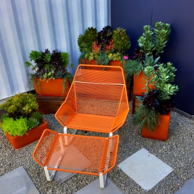 The planter landscape ties the ground and wall planes together to make a rich, visual sense of place for the chair.